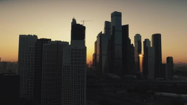 Aerial előtt felhőkarcolók Moszkva város naplemente narancs világos nap között modern acél üvegházak sötét sziluettek városkép. Oroszország tőke üzleti fejlődés futurisztikus kilátás horizont felhő nélküli