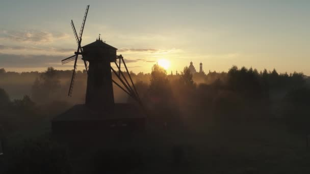 Flight nearby old wooden nursery windmill mill dark silhouette cinematic orange sunrise sun bright rays natural landscape mystical fog forest. Christian orthodox Russian culture church New Jerusalem