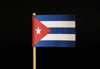 A national flag of Cuba on toothpick and on black background. Cuba is famous for criminality and import and export drugs and cigars. White stars in red field.