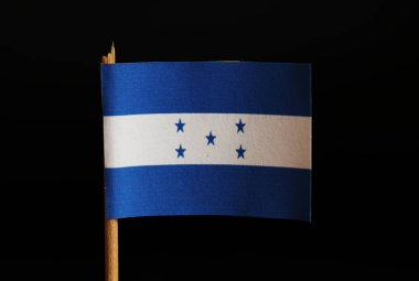 A official flag of Honduras on toothpick and on black background. Honduras is located in central america and belongs to poverty lands. Also is here big unemployment.