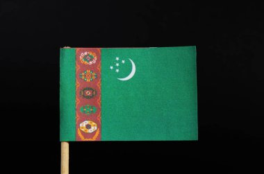 The national flag of Turkmenistan on toothpick on black background. A green field with a vertical red stripe near the hoist side.