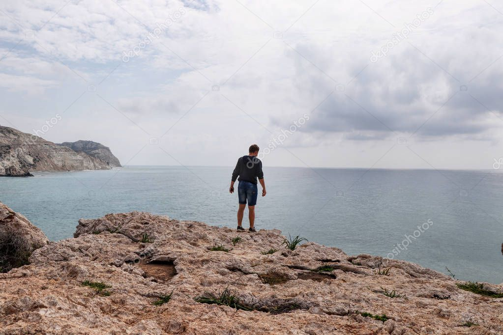 Teenager on the edge of rock Of Greek and watchs waves down. Man is on Aphrodite's rock on Petra de romiou beach. Adolescent climbs on big hill and enjoy scenery and panorama