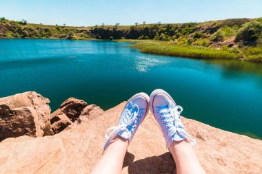 A traveler sits on a cliff overlooking the river and makes a summer selfie