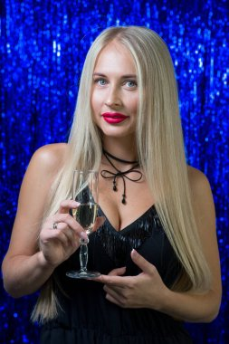sexy girl blonde with red lipstick on her lips holding a glass of champagne and standing in a black outfit on a blue shiny background of a photozone in a nightclub.
