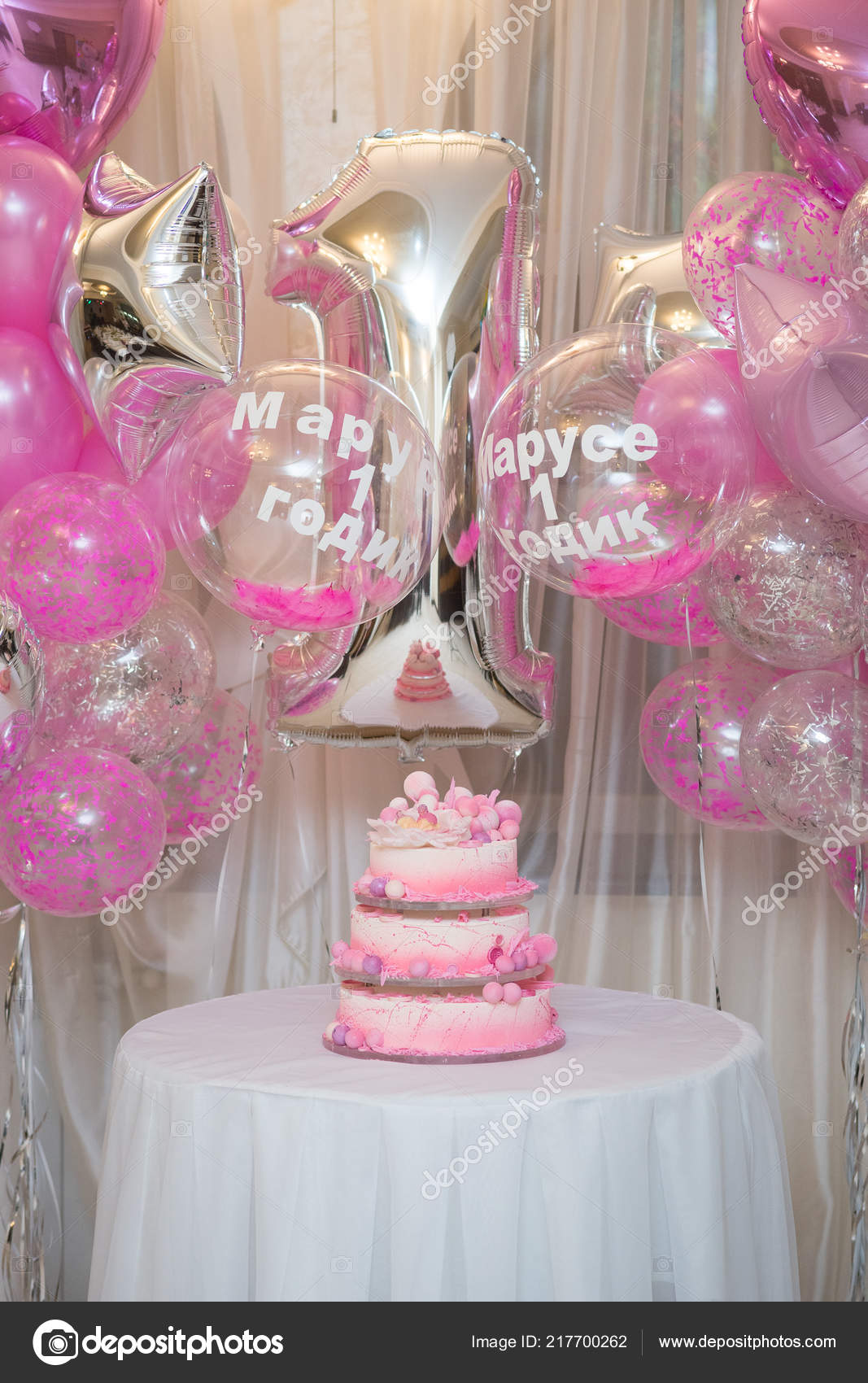 Beautiful Decorated Large Cake From Several Tiers For The First Birthday On A Background Of Decor Balloons With Inscription In Russian Marusya 1 Year