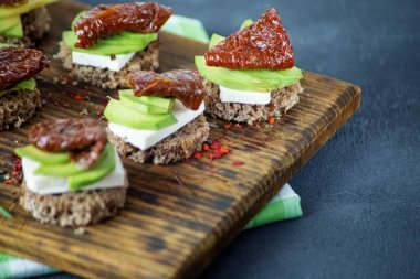 Snacks with cheese, avocado and dried tomatoes on a wooden board. Concept for food, healthy food and vegetarians.
