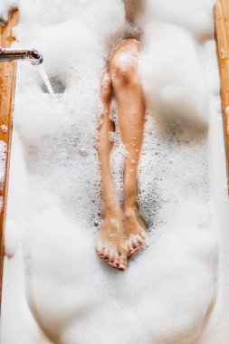 Woman legs in bath foam. Top view. Enjoying and relaxation in spa hotel