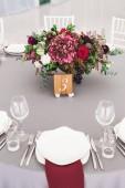 Svatební stůl zdobený červenými květy kytice a šedé ubrus s příbory