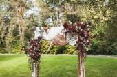 Hochzeitsbogen im rustikalen Stil mit roten Blumen und weißem Textil im Garten
