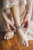 Nevěsta na sobě stříbrná kovová ozdoba náramek na nohu, krásné béžové krajkové šaty