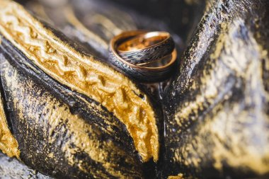 Two black and gold wedding rings on stone painted multicolor background