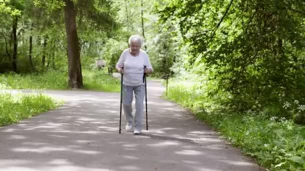 Oma spaziert mit Stöcken zum Nordic Walking in den Park