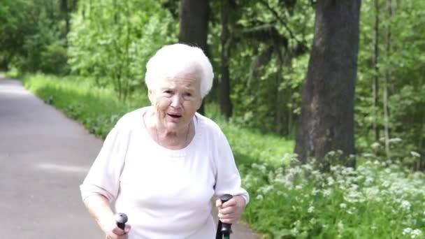 Babička chodí s holí na Nordic walking stará šedá