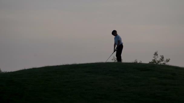 Silhouette der jungen Golfer mit Golf-Bag bei Sonnenuntergang