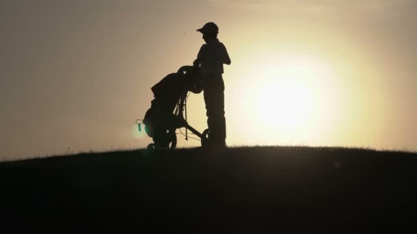 Silhouette of boy golfer with golf bag at sunset