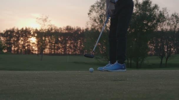Junior golf player je odkládali míč z díry