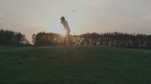 Boy golfového hráče udeřit železo z plavební dráhy na golfovém hřišti