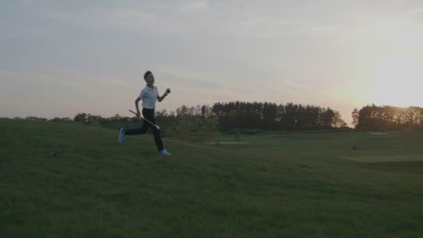 Fröhlicher junge Golfer. Fröhliche junior jungen auf dem Golfplatz bei Sonnenuntergang