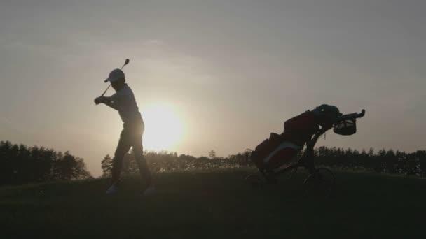 Silueta chlapec golfista s golfový bag při západu slunce