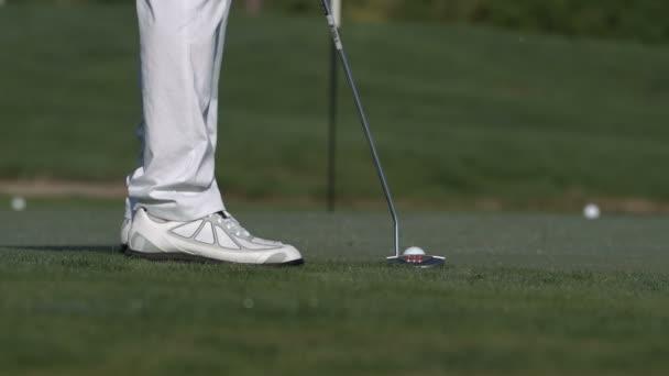 mužské golfista uvedení golfový míček v otvoru