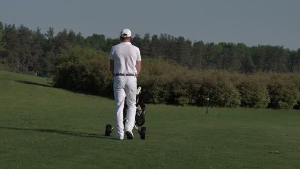 Muž golfista brašna a pěšky k další jamce na golfovém hřišti
