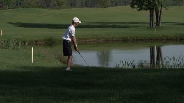 Junior golfista hrát golf na léto s bít střílel na zelené trávě