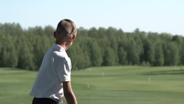 Junior golfer playing golf on summer with hitting shot on green grass