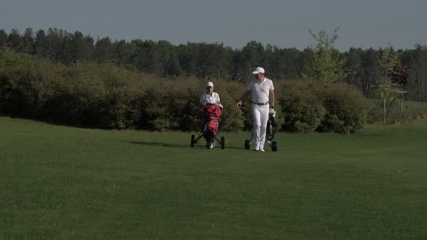 Happy man with his son golfers walking on perfect golf course at summer day