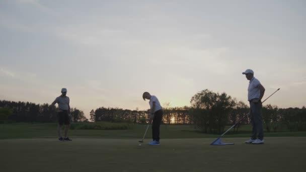 Dva golfisté s junior golfisté chůzi na perfektní hřiště na západ slunce na den