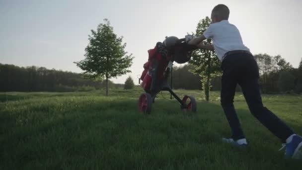 Šťastný chlapec golfista. Veselé dětské chlapce na golfovém hřišti při západu slunce