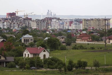 Wide beautiful summer panorama of quiet suburban area with nice comfortable cottages and green gardens on background of modern developing city with high buildings and working constructions cranes.