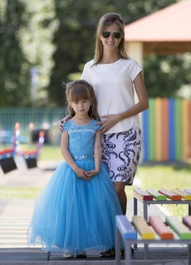 Full-length portrait of young blond slim smiling happily mother in sunglasses and small pretty daughter girl in long blue evening dress on kindergarten blurred playground. Care and love concept.