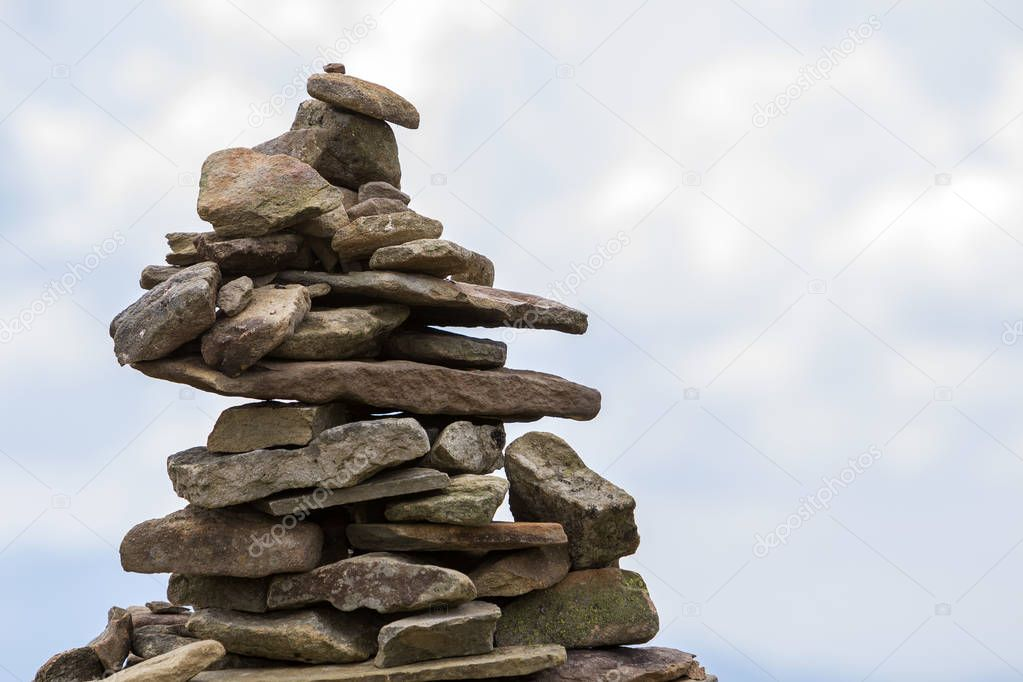 Close-up abstract image of rough natural brown uneven different sizes and forms mountain stones balanced like pyramid pile on bright light blue copy space sky background. Tourism and landmark concept.