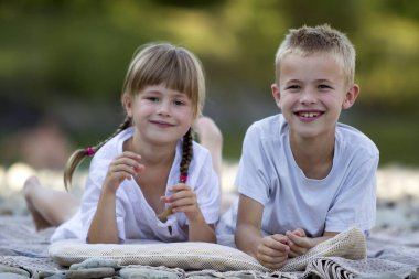 Two young happy cute blond children, boy and girl, brother and sister laying on pebbled beach on blurred bright sunny summer day background. Siblings friendship, leisure and perfect holiday concept.