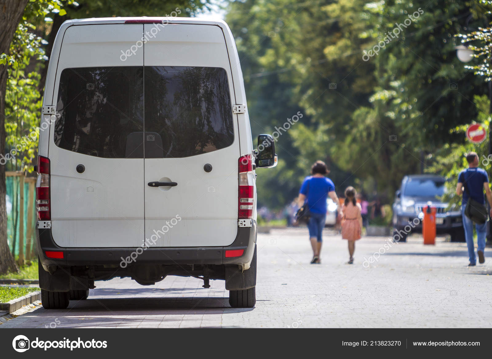 fe282b8667 Back view of white passenger medium size commercial luxury minibus van  parked n shadow of green tree on summer city street with blurred  silhouettes of ...