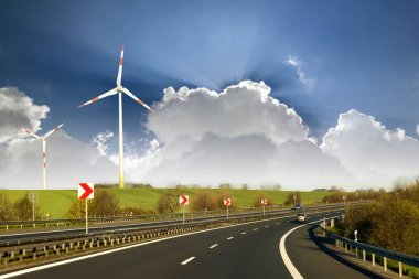 Wide highway with moving car stretching to horizon by green hills with high wind turbines on blue cloudy sky background. Modern technologies, renewable energy source and ecological problems solving.