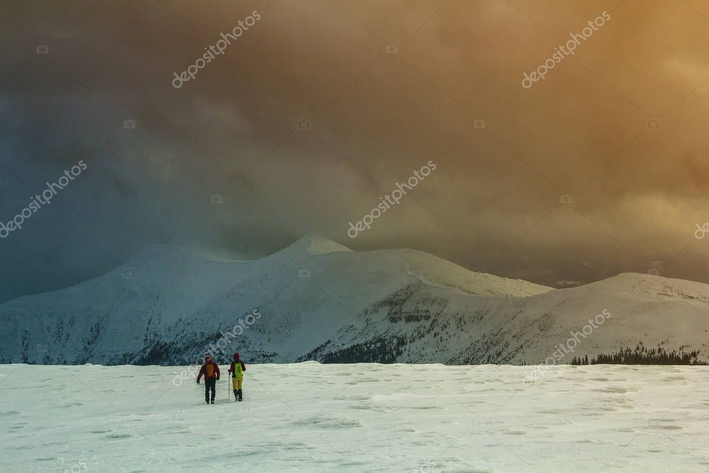 Winter panorama. Back view of two tourists hikers with backpacks going in snowy valley to magnificent mountain range under gloomy cloudy sky. Active lifestyle, tourism and extreme sports concept.