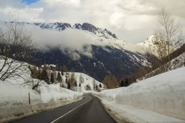 Empty twisty asphalt road stretching through deep snow towards beautiful bright white Alps steep rocky woody snowy mountain peaks under cloudy winter sky. Winter landscape on cold sunny day.