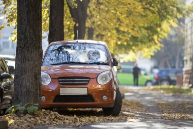 Front view of small orange mini car parked in quiet yard on sunny autumn day on blurred buildings and big old trees golden foliage bokeh background. Transportation, parking problems concept.