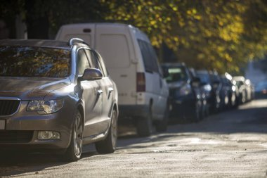 Long row of cars parked along roadside on sunny autumn day on blurred green golden foliage bokeh background. Transportation, modern city lifestyle, vehicles parking problems concept.