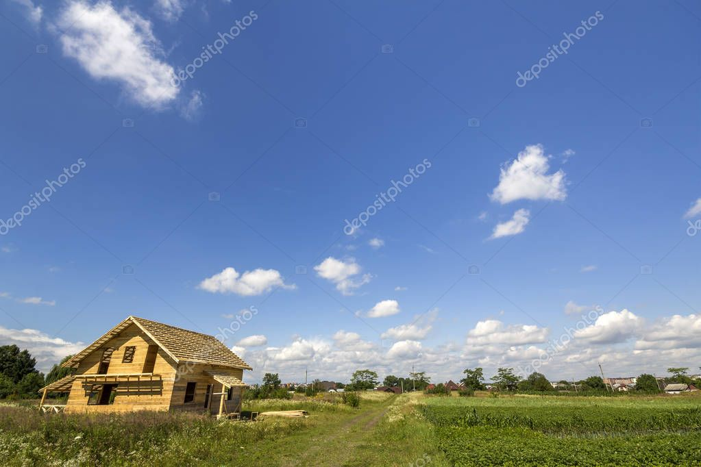 New wooden ecological not finished cottage from natural materials under construction in green field on distant village and blue sky copy space background. Old traditions and modern building concept.