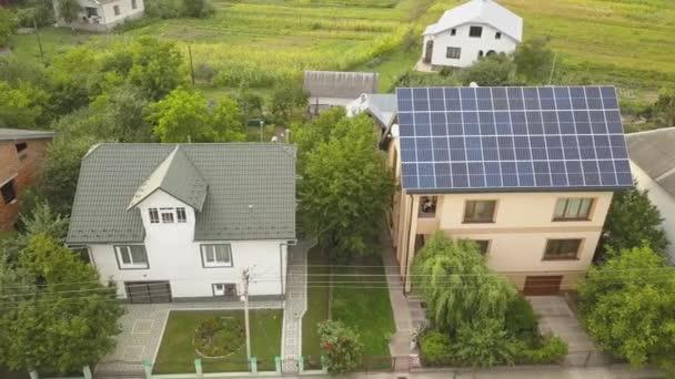 Luftaufnahme des neuen modernen Wohnhauses Hütte mit blau glänzenden Solar-Photovoltaik-Panel-System auf dem Dach. Erneuerbare ökologische Ökoenergie-Produktionskonzept.