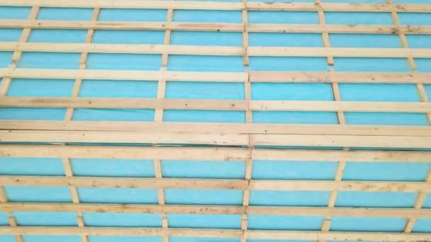 Letecký pohled na cihlový dům s dřevěným střešním rámem ve výstavbě.