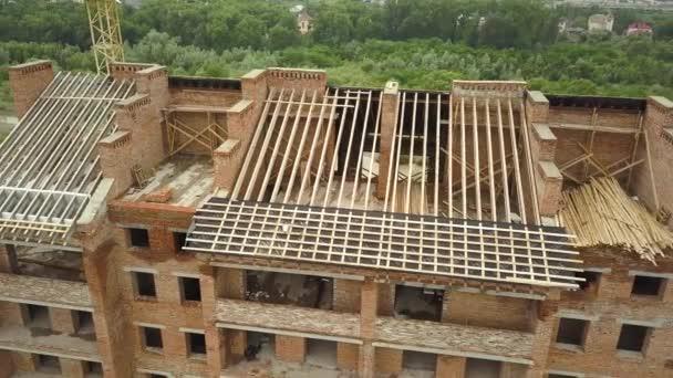 Luftaufnahme eines unfertigen Backstein-Wohnhauses mit Holzdachkonstruktion im Bau.