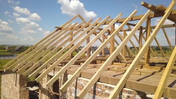 Luftaufnahme eines unfertigen Hauses mit im Bau befindlicher hölzerner Dachkonstruktion.