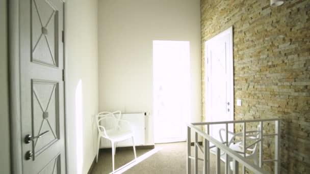 Interieur eines modernen Hauses mit geräumigem Flur, Zimmertüren und Treppengeländer im modernen Stil.
