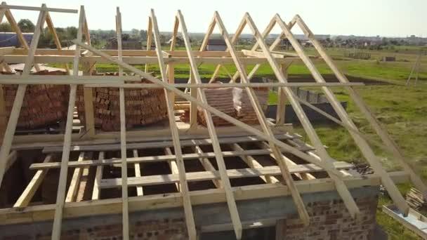 Luftaufnahme eines unfertigen Backsteinhauses mit im Bau befindlicher hölzerner Dachkonstruktion.