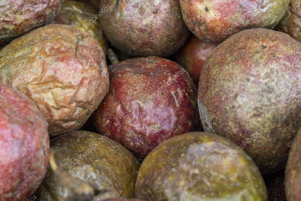 Dried passion fruit bunch on market, closeup photo. Passion fruit texture. Red and brown exotic fruit. Pile of tropical fruits. Ripe sweet tropical fruit with juicy meat. Vitamin food background