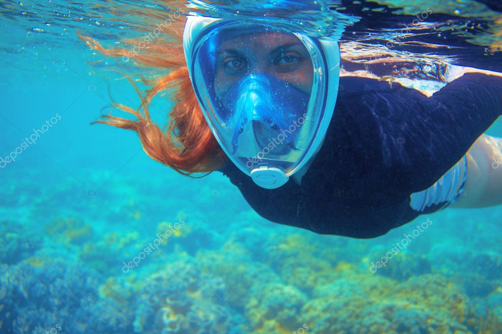 Red hair snorkeling girl full-face snorkeling mask in coral reef. Snorkel in coral reef of tropical sea. Underwater photo of oceanic landscape. Active seaside vacation. Seaside activity