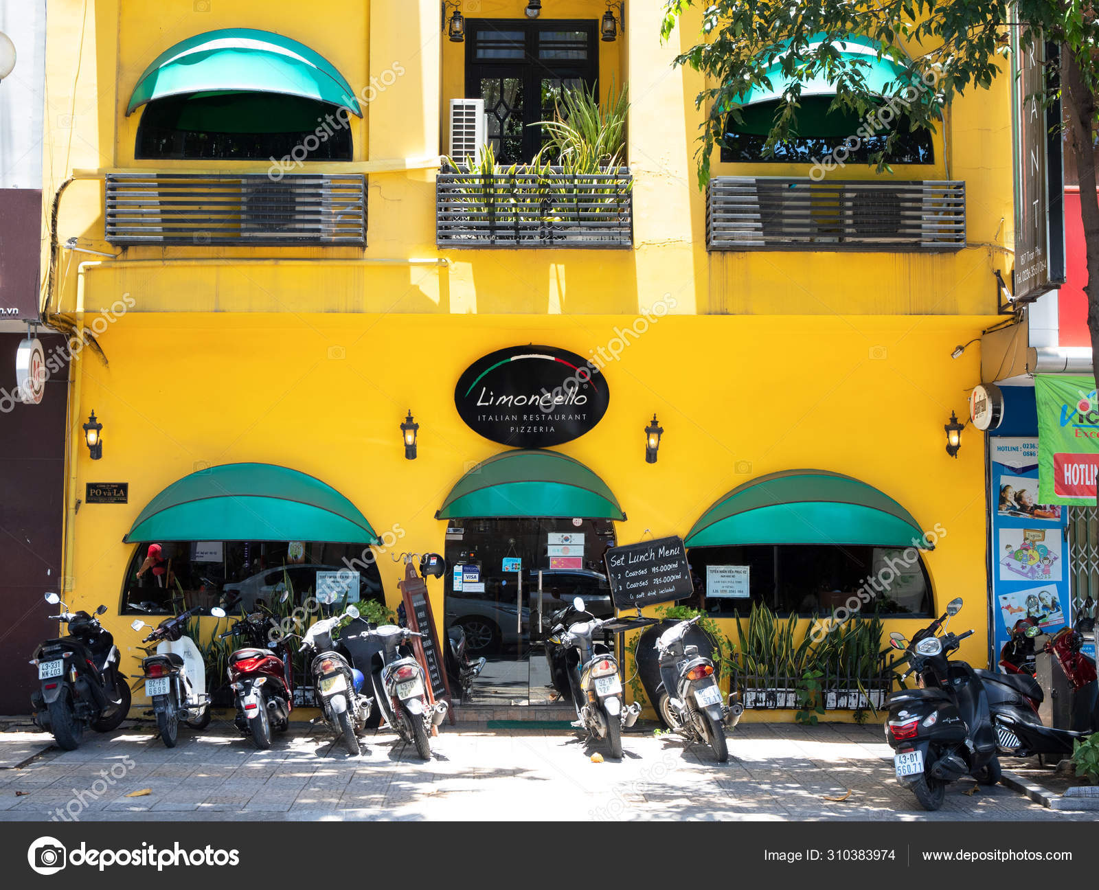 Danang Vietnam 27 Jul 2019 Cozy Cafe In Yellow Building With Green Tents And Motorbikes On Parking Bright Exterior Of Cafe Or Coffee Shop Stock Editorial Photo C Davdeka 310383974